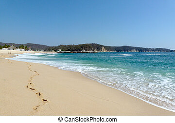 Huatulco beach with footprints - Footprints in the sand of...