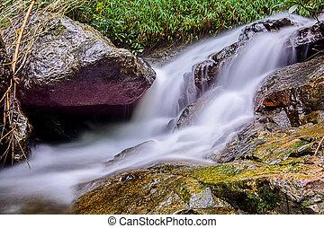 Beautiful silky waterfall flow through stones, Huay Kaew Waterfall, Chiang mai Province, Thailand.