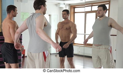 hubby man and athlete bodybuilder look at themselves in the mirror in the gym