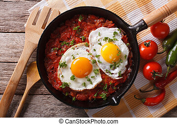 huevos rancheros closeup in the pan and ingredients,...