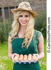 huevos, tenencia, sonriente, cartón, mujer, rubio, joven
