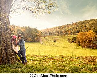 Hug in the autumn park under a tree