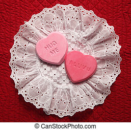 two heart candy replicas on an eyelet doily