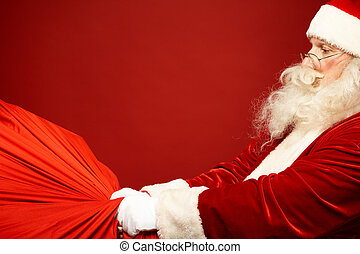 Huge and heavy sack - Portrait of Santa Claus carrying huge...