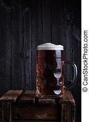 Huge beer mug on vintage wooden crate with dark wooden...