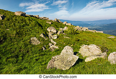 huge boulders on a grassy slope in mountains. lovely...