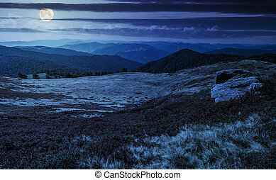 huge boulders on the edge of hillside at night in full moon...