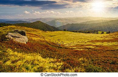 huge boulders on the edge of hillside at sunset - huge...