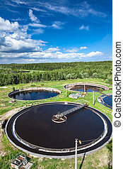 Huge circular settlers of sewage treatment plant under blue...