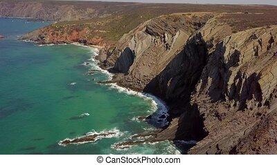 Huge cliffs on ocean shore - Aerial panorama of blue ocean...