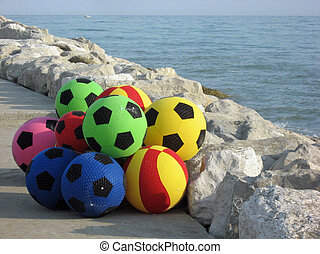colorful balloons playing on the rocks near the sea to...