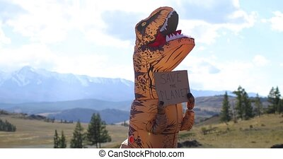 Huge dinosaur doll Tyrannosaurus Rex with person inside is holding banner save the planet in paws. Nature park in mountains. Concept of environmental protection. Installation with prehistoric animal.