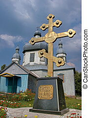 Huge golden christian cross near old wooden church in Lebedin, Ukraine