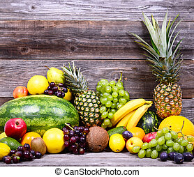 Huge group of fresh colorful fruit on wooden background - Health