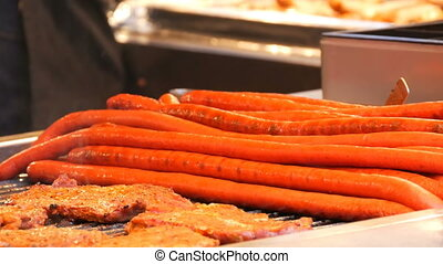 Huge half-meter long red sausages and meat chops with steam...