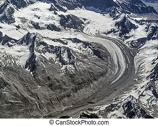 Huge high mountains glacier: the moraine ice tongue curves among the snow-capped mountain peaks and arc descends into the valley of Ladakh, Tibet, India.