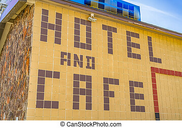 Huge Hotel And Cafe sign on the exterior wall of a building with outdoor lights