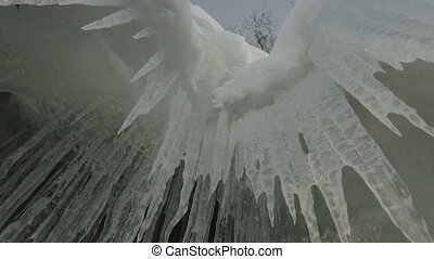 Huge icicles on rocks. Beautiful winter Lake Baikal.