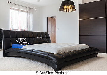 Huge leather bed in bedroom