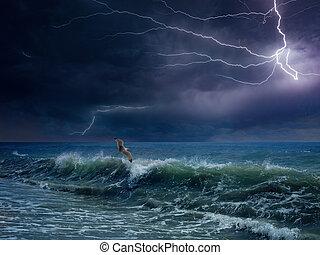 Huge lightning in dark sky above stormy sea