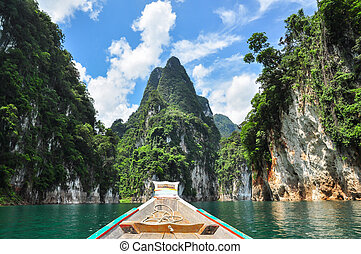 Huge limestone cliffs rising out of open lake at Khao Sok...