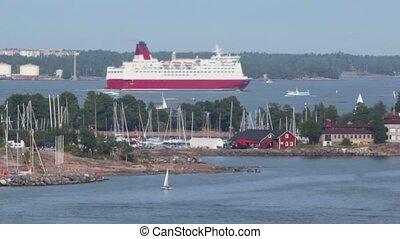 Huge liner among smaller vessels float near coastline