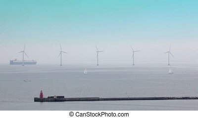 Huge liner and several yacht float in sea with windmills around