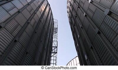 Huge metal buildings, up view. High metal grain storage...