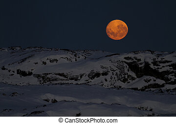 huge moon in the night sky over one of the Antarctic islands