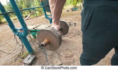 Huge muscular male hand raising heavy iron dumbbell in the...