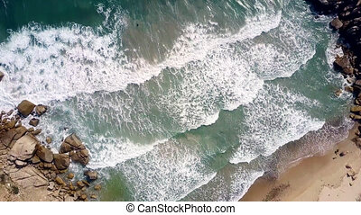 huge ocean waves roll on beach clutched in narrow passage -...