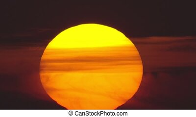 Huge orange sun with clouds, fast sunrise - Closeup of huge...