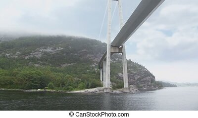 Huge pendant bridge at coast with forest on mountains