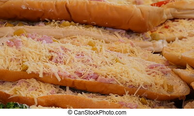 Huge piece of loaf on top of which is sausage, grated cheese...