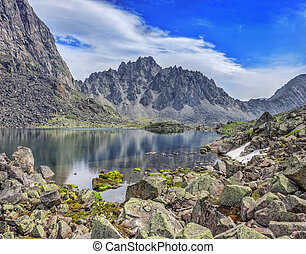 Huge pieces of granite on the lake in the mountains of...