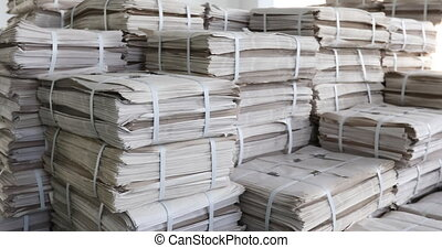 Huge piles of printed newspapers printing shop.