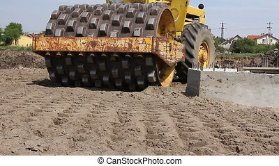 Huge road roller with spikes is compacting soil at...