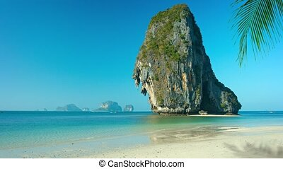 UltraHD video - Huge formation of crumbling limestone, towering against the horizon, over a beautiful, tropical, white sand beach.
