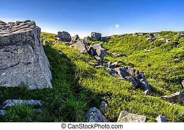 huge stones in valley on top of mountain range at sunrise -...