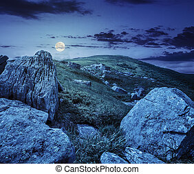 huge stones in valley on top of mountain range at night -...
