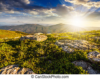 huge stones in valley on top of mountain range at sunset -...