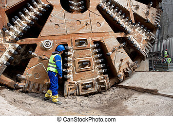 huge tunnel boring machine - Construction worker looking at...