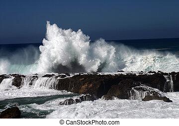 Huge wave is crashing on a wall of rocks.