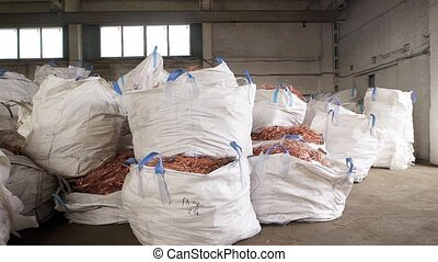 huge white bags with copper scrap from wires are lying in a...