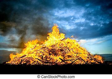 huge wood fueled bonfire burning at sunset