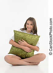 Hugging a pillow. Cheerful teenage girl hugging a pillow and looking at camera while isolated on white
