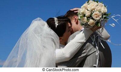 hugging bride and bridegroom kissing outdoor, blue sky in background