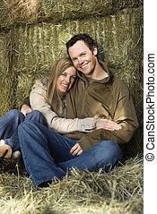 Hugging couple in hay.