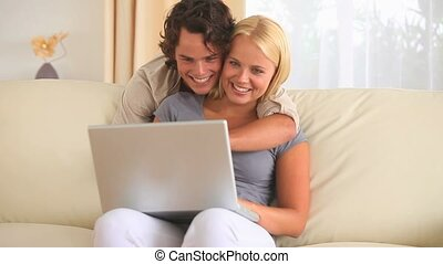 Hugging couple looking at a laptop