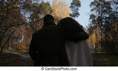 Hugging couple walking in park